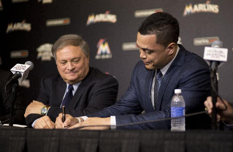 Giancarlo Stanton signs his deal with the Marlins. (AP)