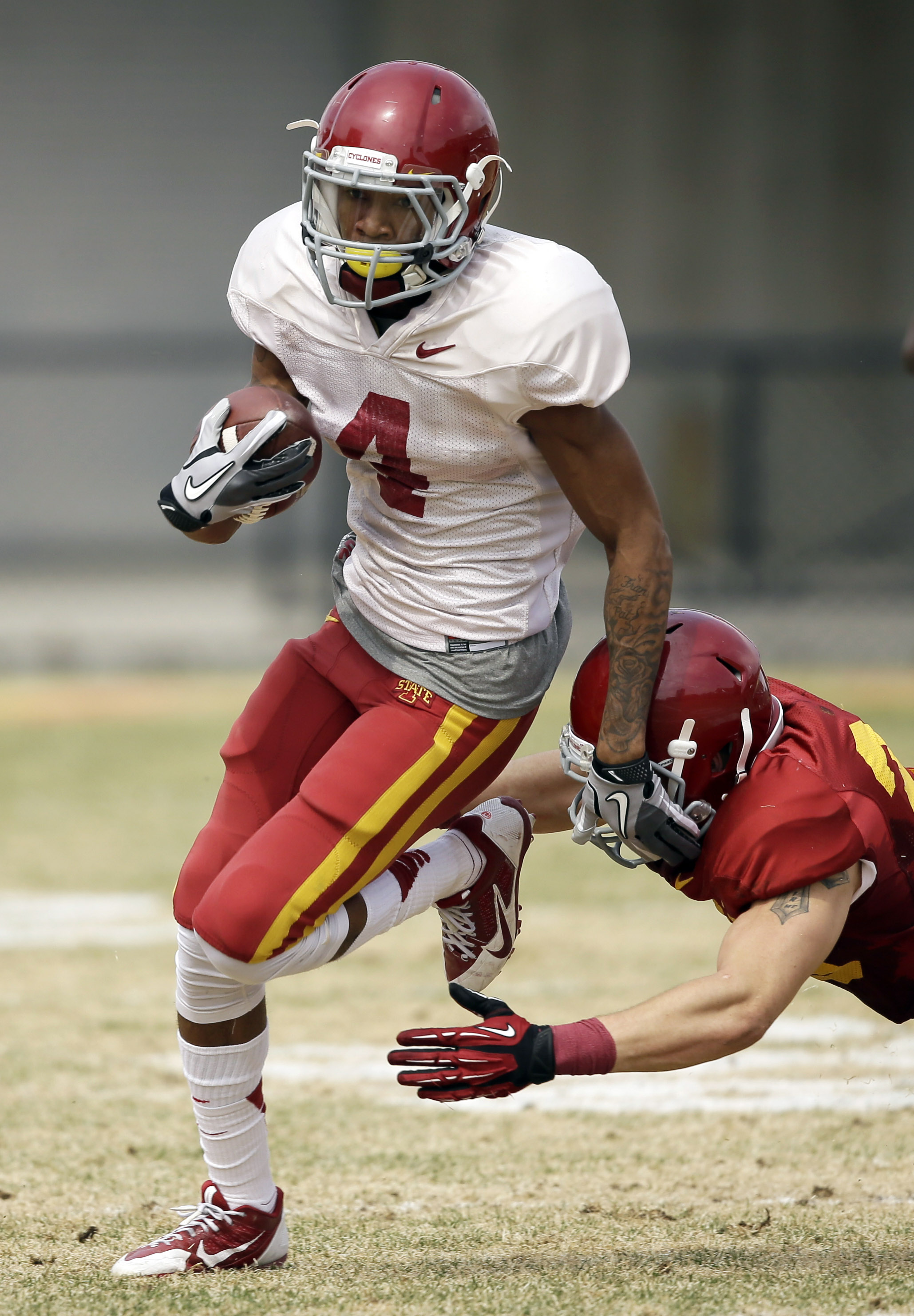 Iowa State wide receiver P.J. Harris runs from defensive back Darian Cotton, right, after making a reception during an annual NCAA college spring football game on Saturday, April 12, 2014, in Ames, Iowa. (AP Photo/Charlie Neibergall)