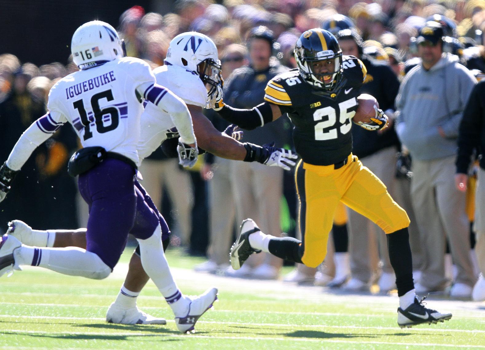 Iowa running back Akrum Wadley (25) stiff arms Northwestern linebacker Chi Chi Ariguzo (44). Saturday, Nov. 1, 2014, in Iowa City, Iowa . (AP Photo/Justin Hayworth)