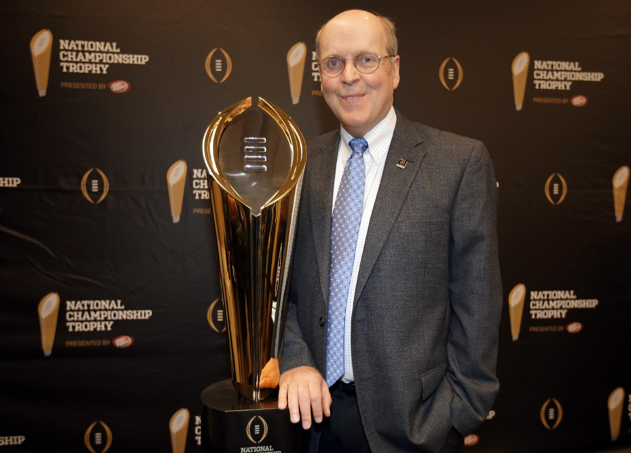 College Football Playoff Executive Director Bill Hancock poses with the College Football Playoff National Championship Trophy in Irving, Texas. (AP Photo/Tony Gutierrez, File)