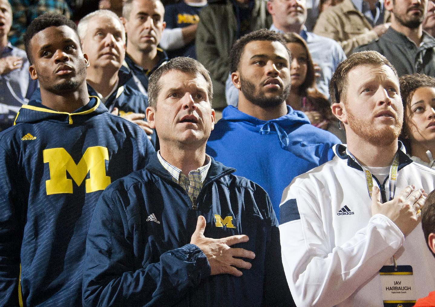 Michigan football head coach Jim Harbaugh, center, stands for the national anthem with son Jay, right, and recruits, before an NCAA college basketball game against Northwestern at Crisler Center in Ann Arbor, Mich., Saturday, Jan. 17, 2015. (AP Photo/Tony Ding)