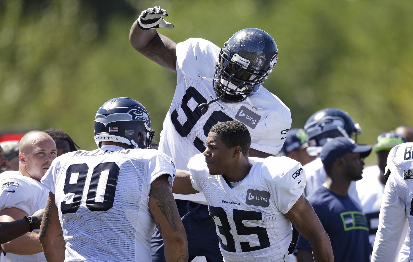 Seattle Seahawks' Tony McDaniel (99) leaps toward teammates Jesse Williams (90) and DeShawn Shead (35) following an NFL football camp practice Tuesday, July 29, 2014, in Renton, Wash. (AP Photo/Elaine Thompson)