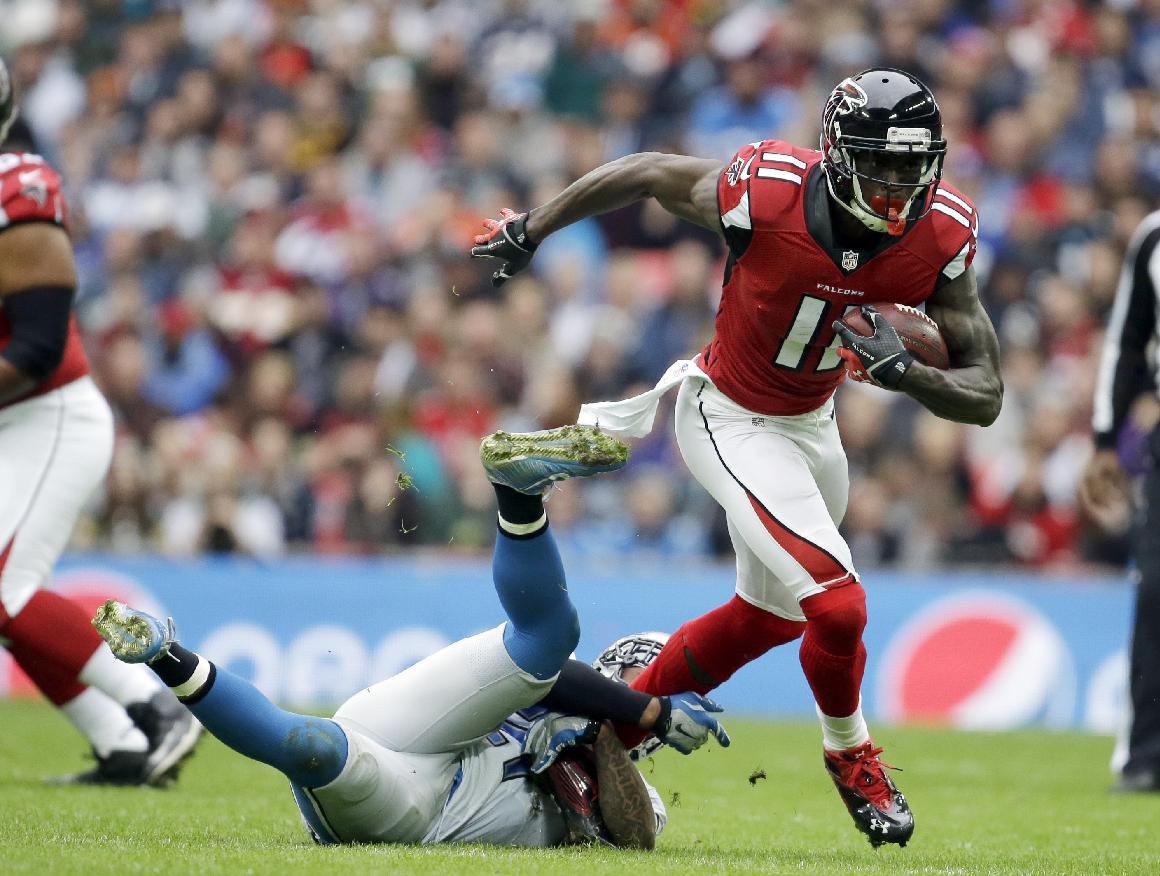 Atlanta Falcons wide receiver Julio Jones (11) runs away from Detroit Lions free safety Glover Quin (27) in the first half of the NFL football game at Wembley Stadium, London, Sunday, Oct. 26, 2014.  (AP Photo/Matt Dunham)