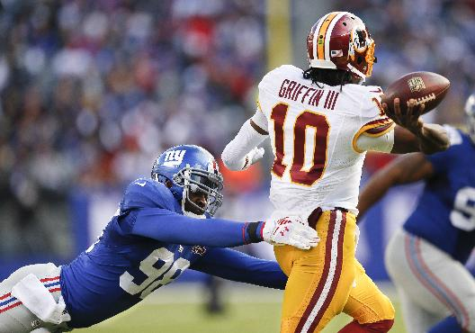 Washington Redskins quarterback Robert Griffin III (10) throws under pressure from New York Giants defensive end Damontre Moore (98) during the second quarter of an NFL football game, Sunday, Dec. 14, 2014, in East Rutherford, N.J. (AP Photo/Julio Cortez)