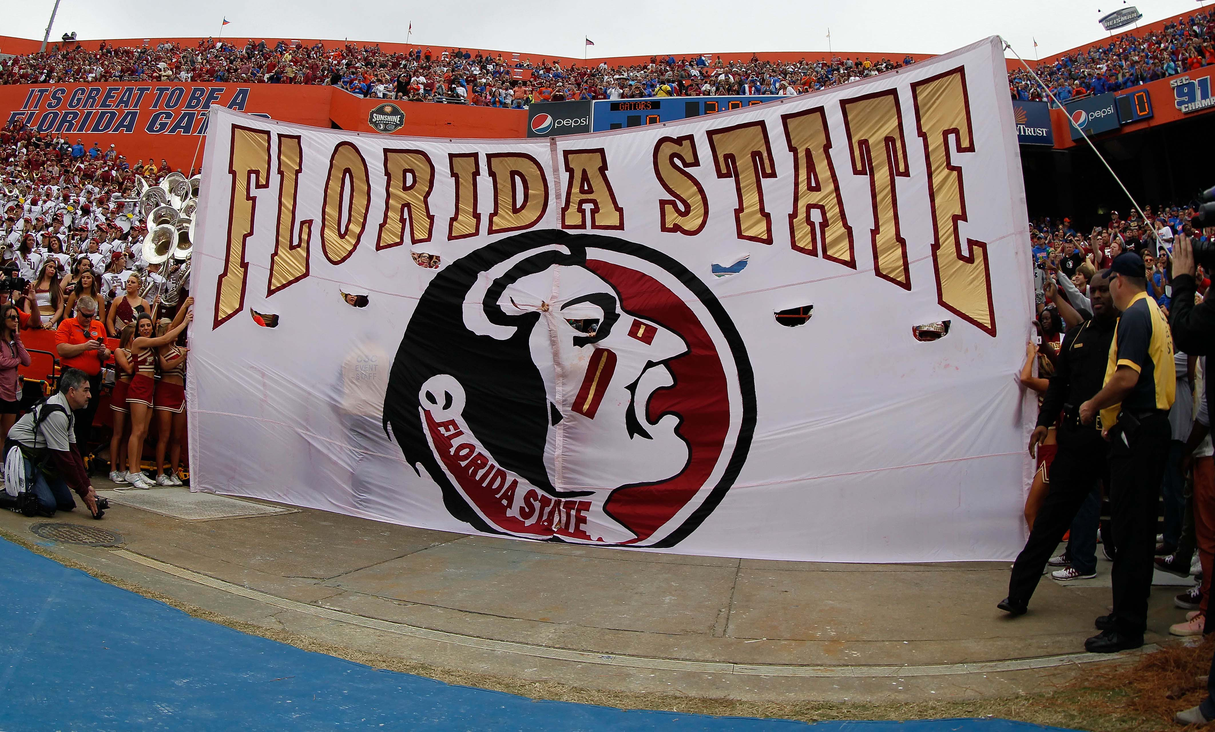 Nov 30, 2013; Gainesville, FL, USA; Florida State flag is held up before the team runs through it against the Florida Gators at Ben Hill Griffin Stadium. (Kim Klement-USA TODAY Sports)
