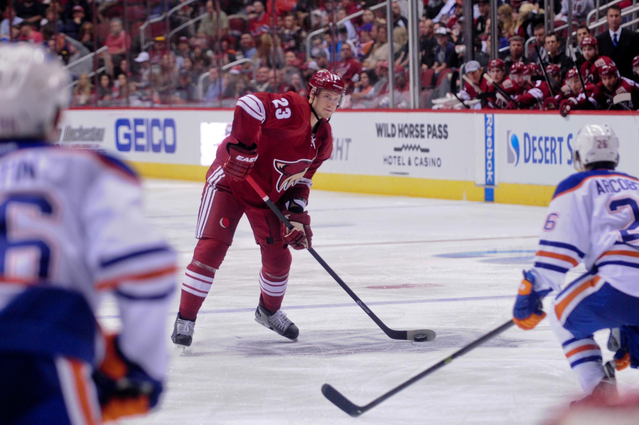Oct 15, 2014; Glendale, AZ, USA; Arizona Coyotes defenseman Oliver Ekman-Larsson (23) shoots the puck as Edmonton Oilers defenseman Nikita Nikitin (86) and center Mark Arcobello (26) defend during the third period at Gila River Arena. (Matt Kartozian-USA TODAY Sports)