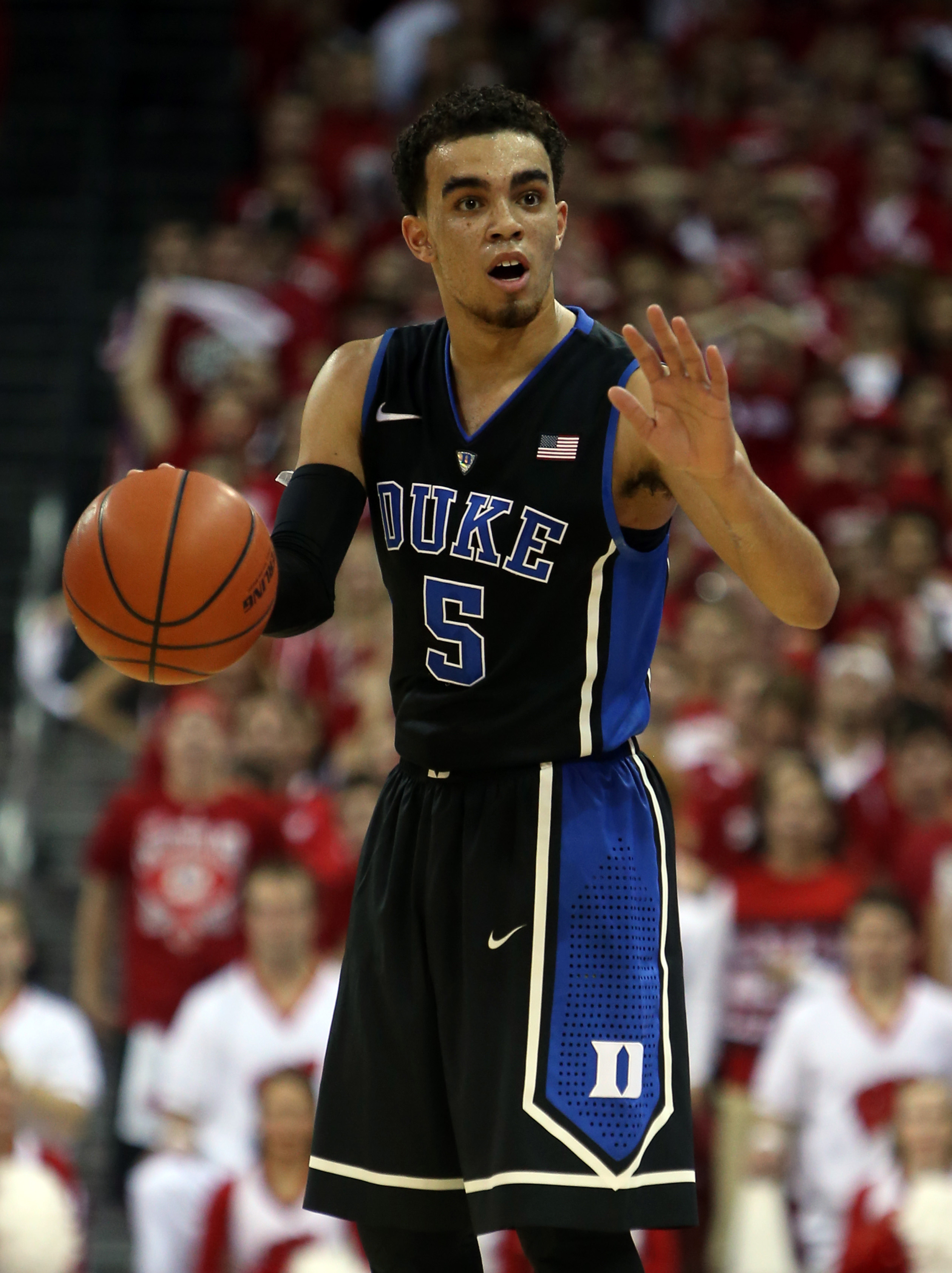 Dec 3, 2014; Madison, WI, USA; Duke Blue Devils guard Tyus Jones (5) signals to his team as they play the Wisconsin Badgers at the Kohl Center. Duke defeated Wisconsin 80-70. (Mary Langenfeld-USA TODAY Sports)