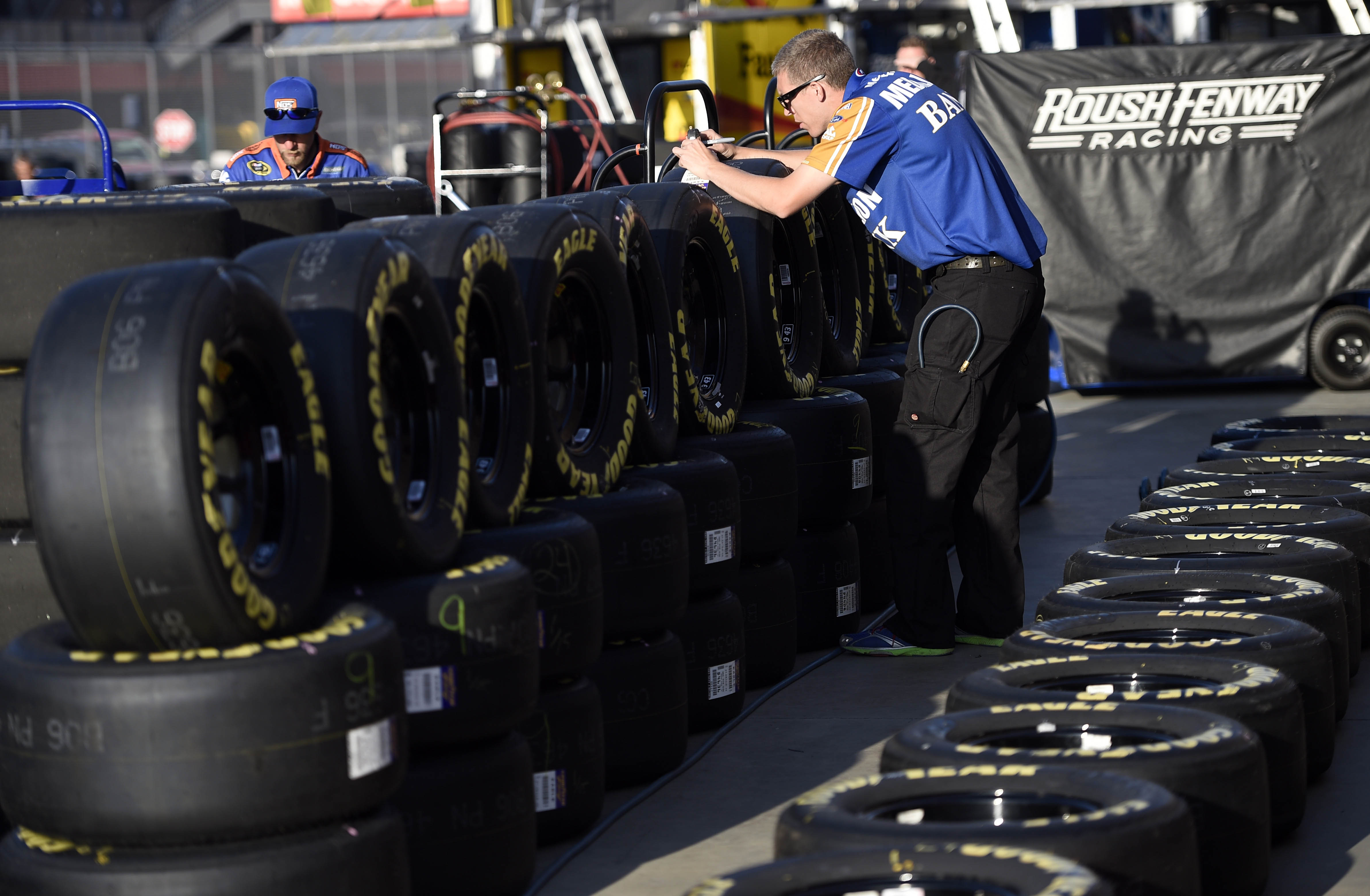 A technician checks tires during practice for the Auto Club 400. (USAT)