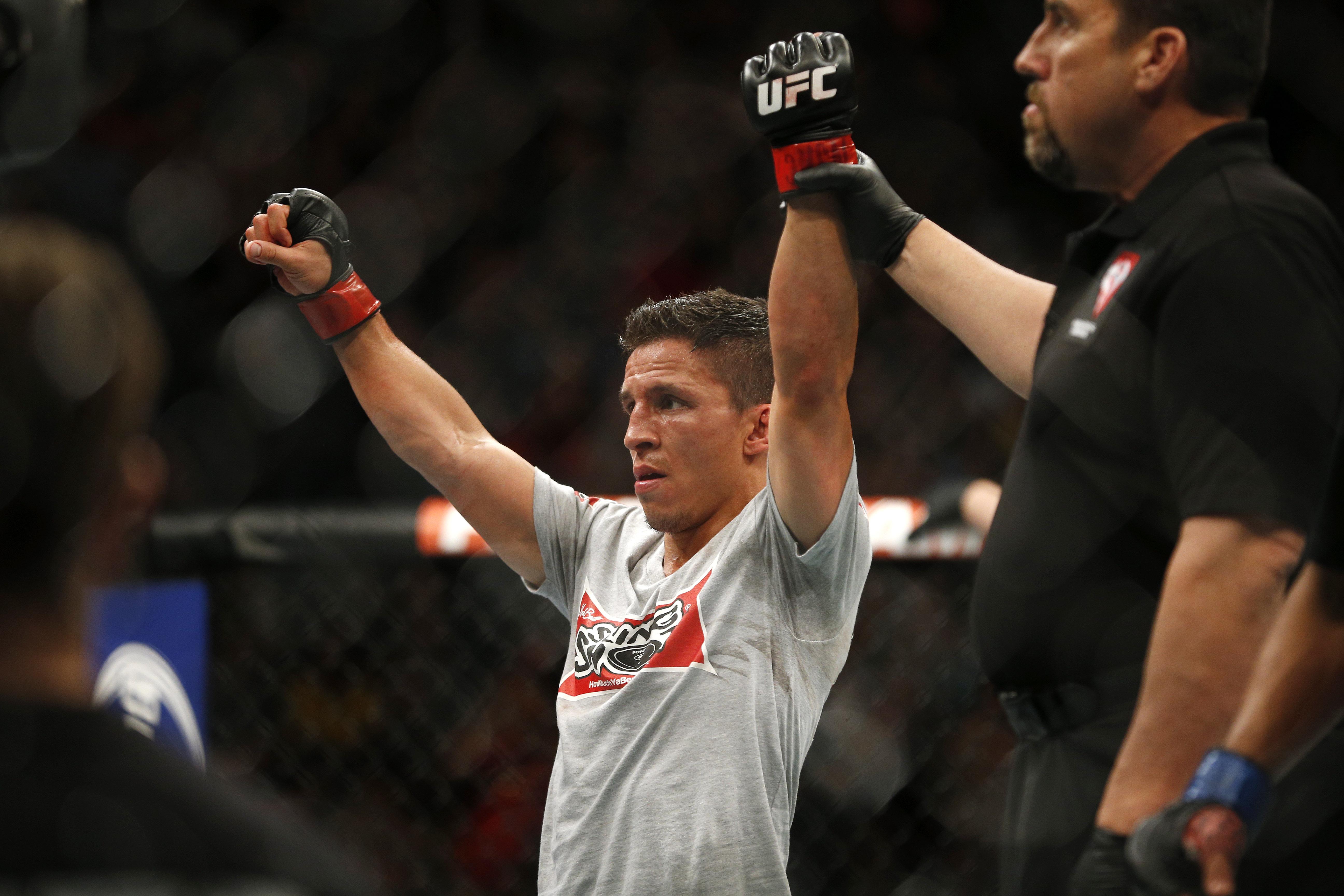 Joseph Benavidez celebrates after defeating John Moraga at UFC 187. (AP)