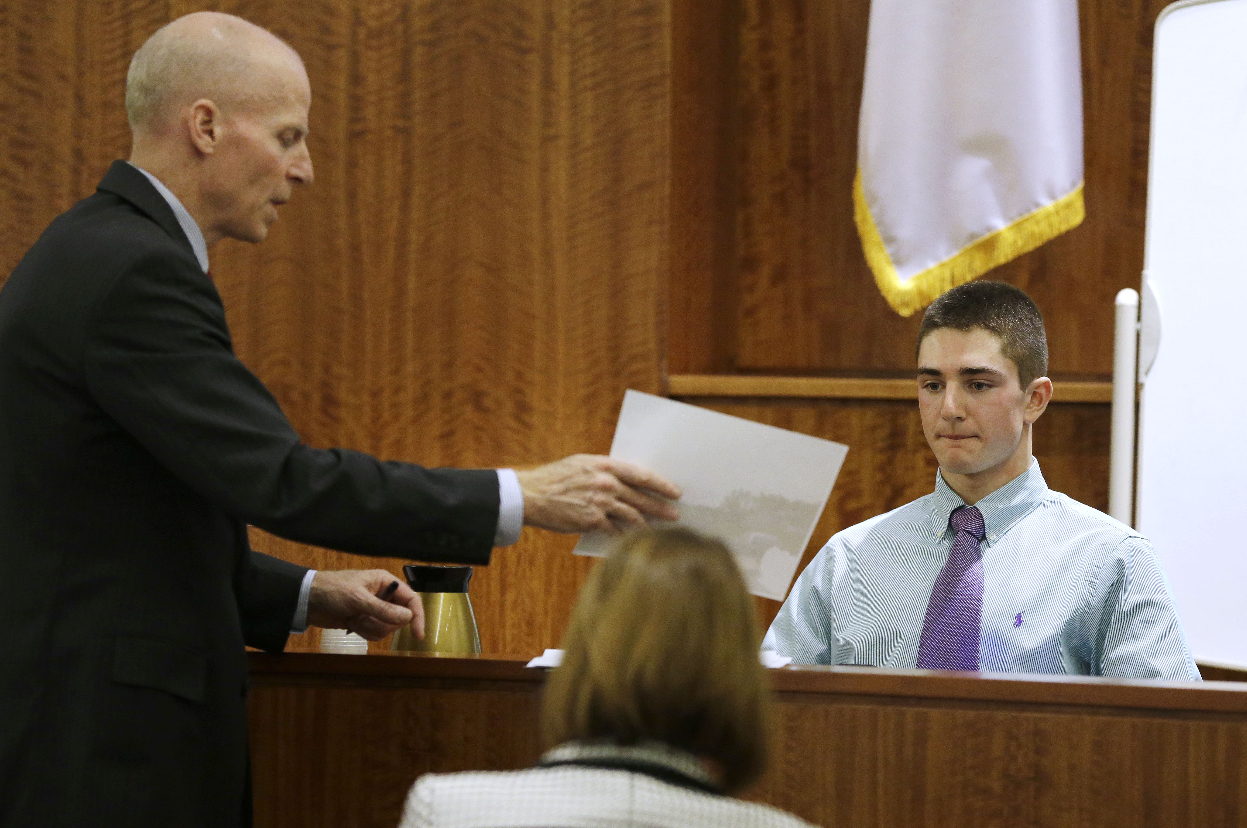 William McCauley, left, shows a witness a photograph. (AP)