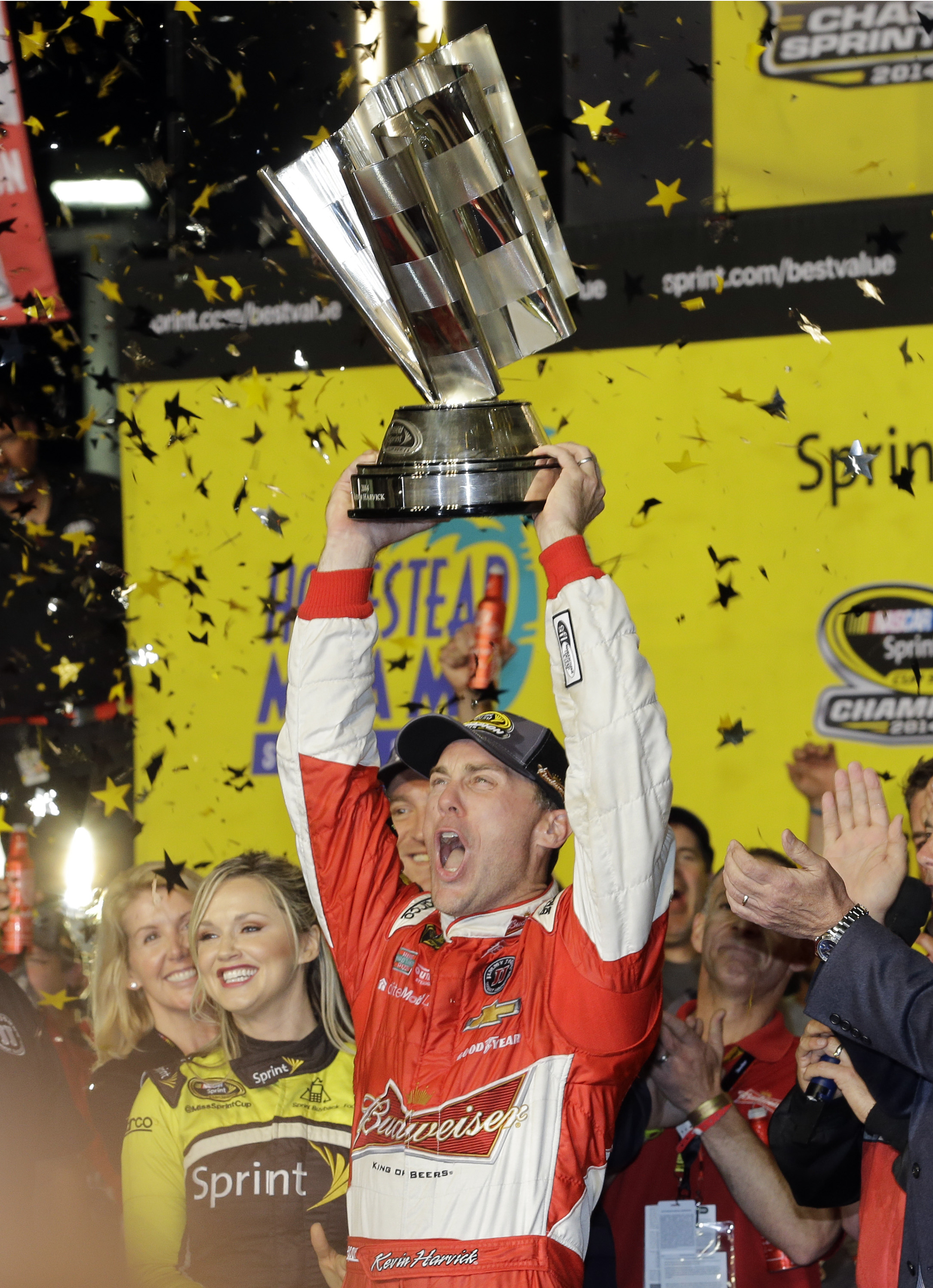 Kevin Harvick raises his trophy as he celebrates after winning the 2014 Sprint Cup championship. (AP)