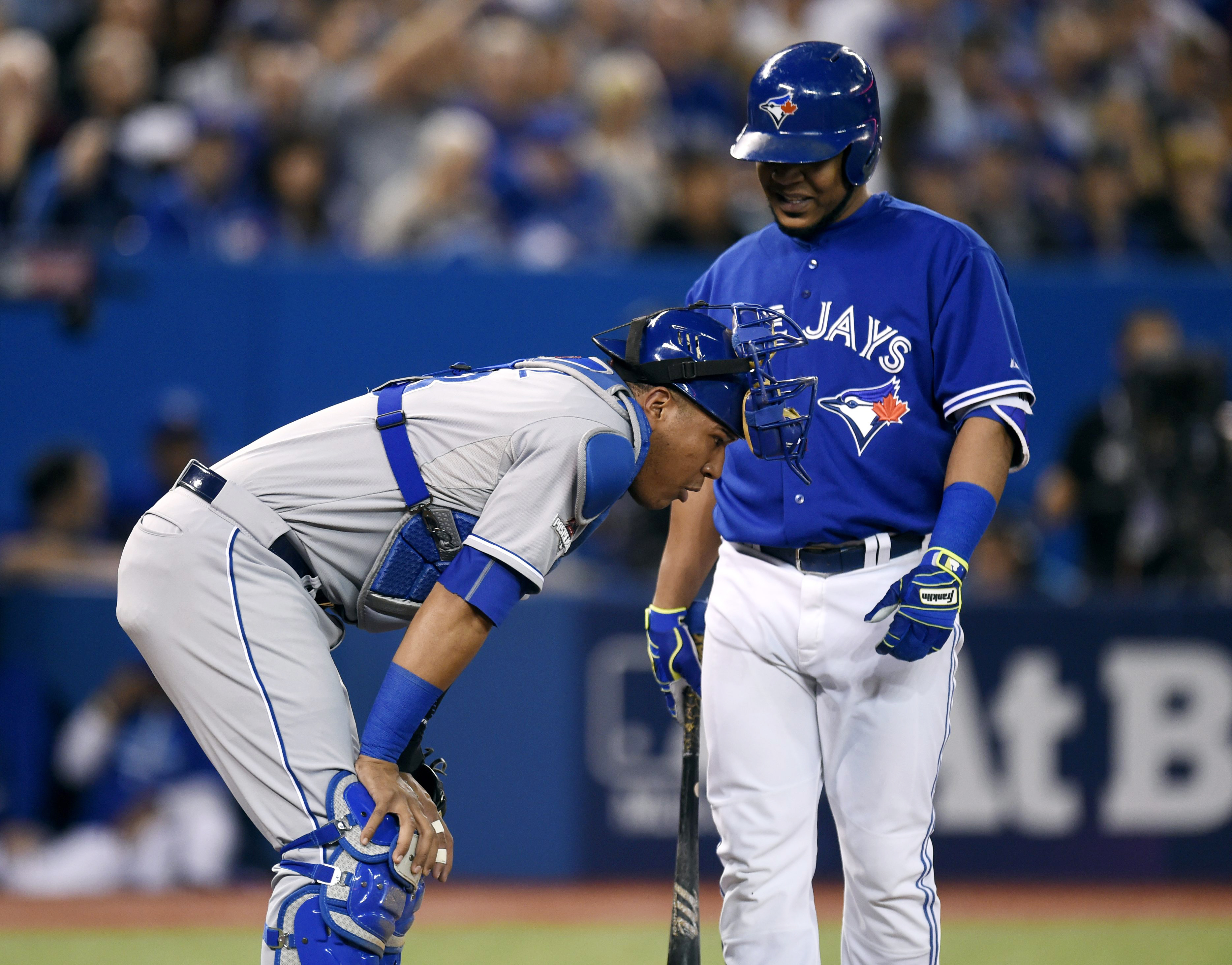 Kansas City Royals' catcher Salvador Perez, left, recovers after getting hit by a foul tip by Toronto Blue Jays' designated hitter Edwin Encarnacion during the first inning in Game 4 of baseball's American League Championship Series on Tuesday, Oct. 20, 2015, in Toronto. (Frank Gunn/The Canadian Press via AP) MANDATORY CREDIT