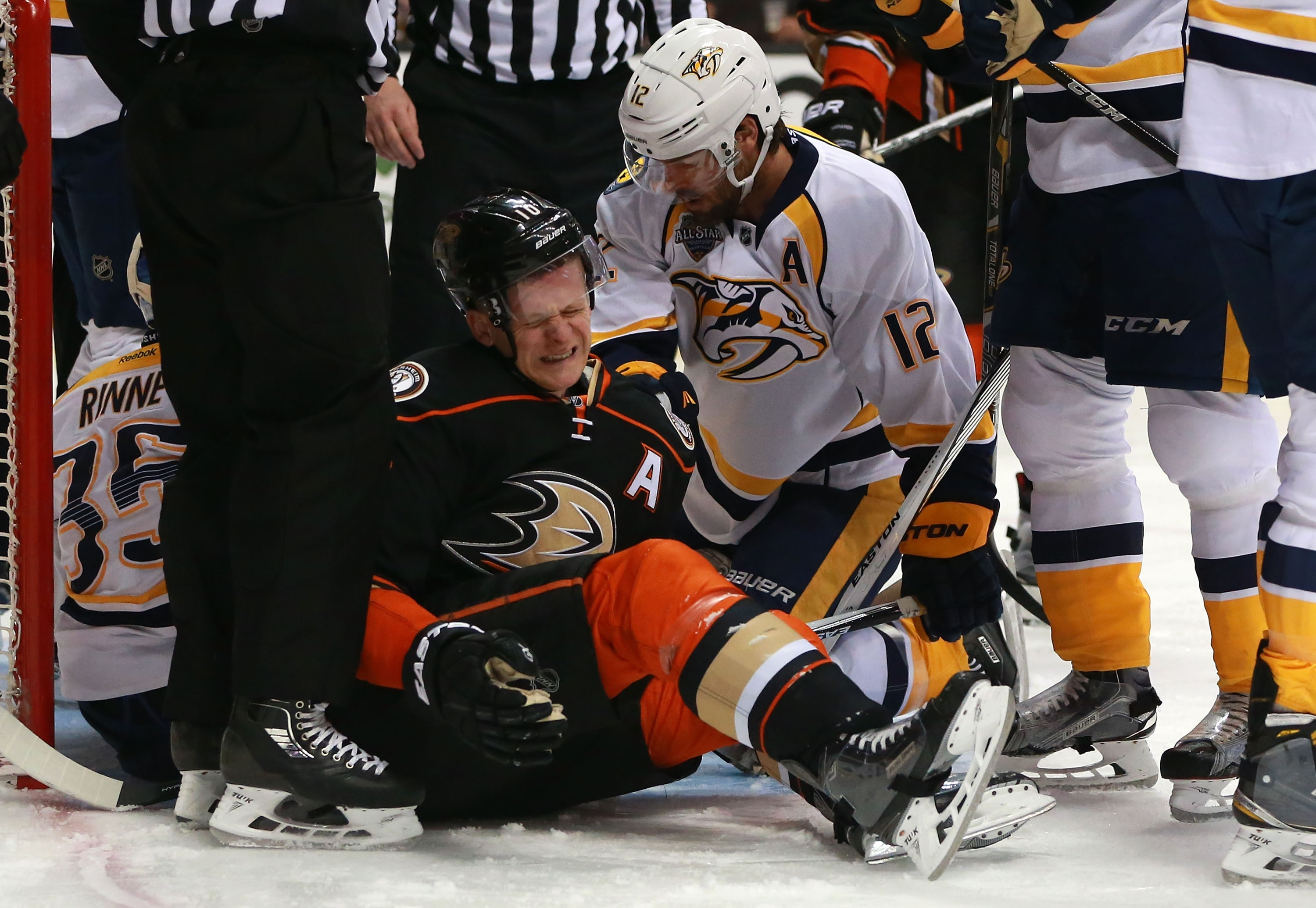 ANAHEIM, CA - APRIL 23: Corey Perry #10 of the Anaheim Ducks winces in pain after a play where he was check hard to the ice into the Predators crease area as Mike Fisher #12 of the Nashville Predators looks on in the first period of Game Five of the Western Conference First Round during the 2016 NHL Stanley Cup Playoffs at Honda Center on April 23, 2016 in Anaheim, California. The Ducks defeated the Predators 5-2. (Photo by Victor Decolongon/Getty Images)