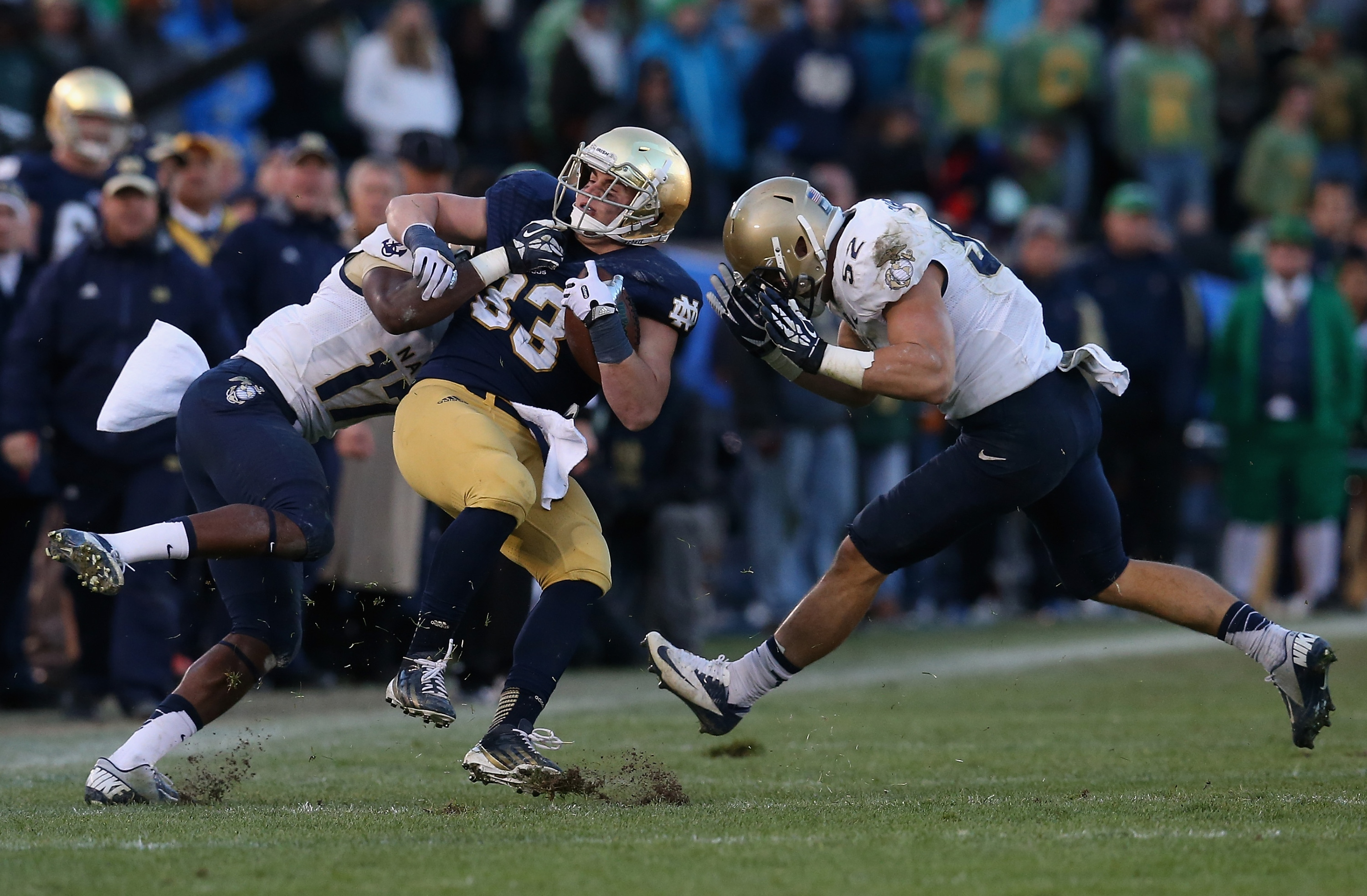 SOUTH BEND, IN - NOVEMBER 02: Cam McDaniel #33 of the Notre Dame Fighting Irish is hit by Kwazel Bertrand #17 and D.J. Sargenti #52 of the Navy Midshipmen at Notre Dame Stadium on November 2, 2013 in South Bend, Indiana. Notre Dame defeated Navy 38-34. (Photo by Jonathan Daniel/Getty Images)