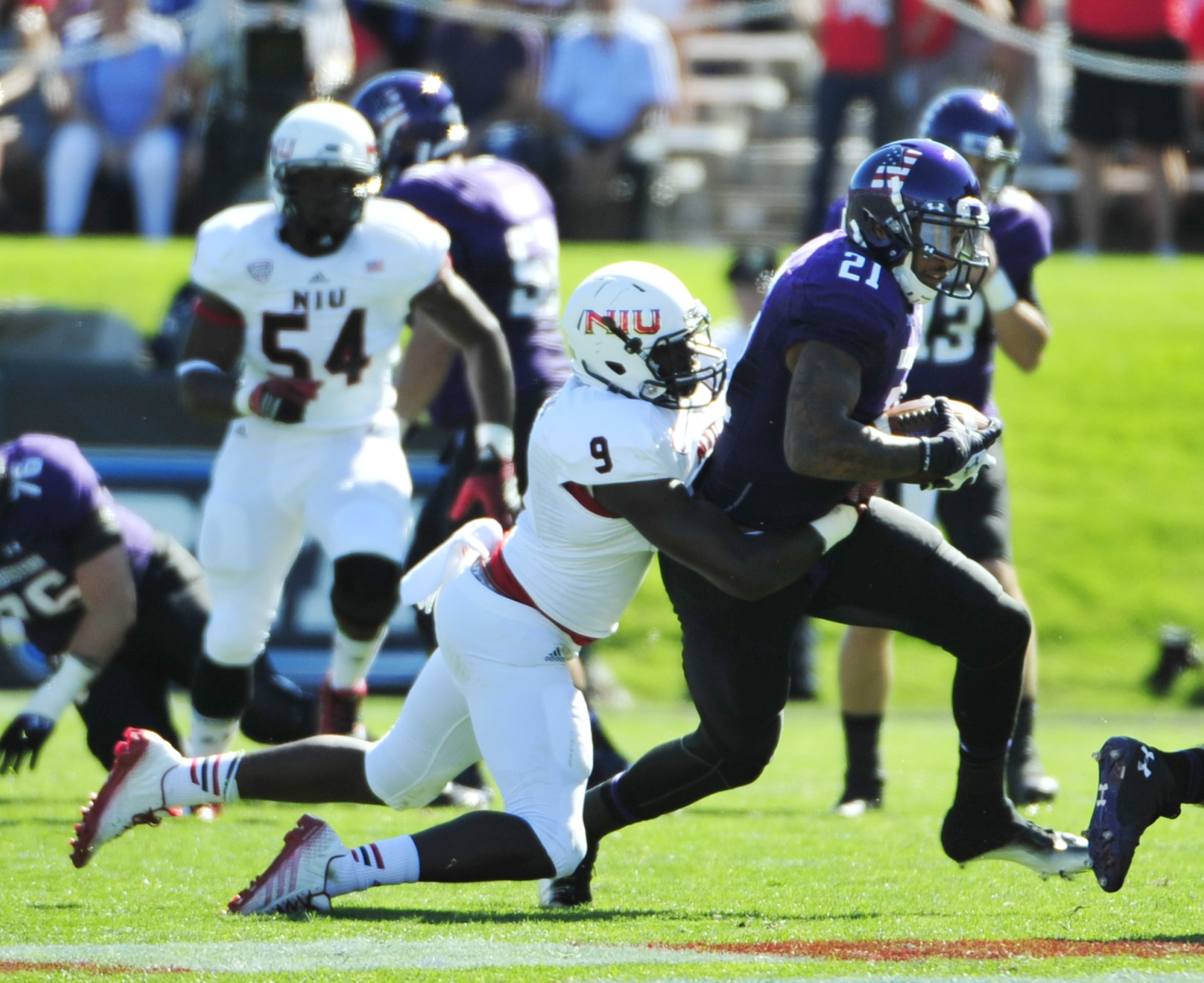 EVANSTON, IL- SEPTEMBER 06: Kyle Prater #21 of the Northwestern Wildcats* is tackled by Rasheen Lemon #9 of the Northern Illinois Huskies on September 6, 2014 at Ryan Field in Evanston, Illinois. (Photo by David Banks/Getty Images)
