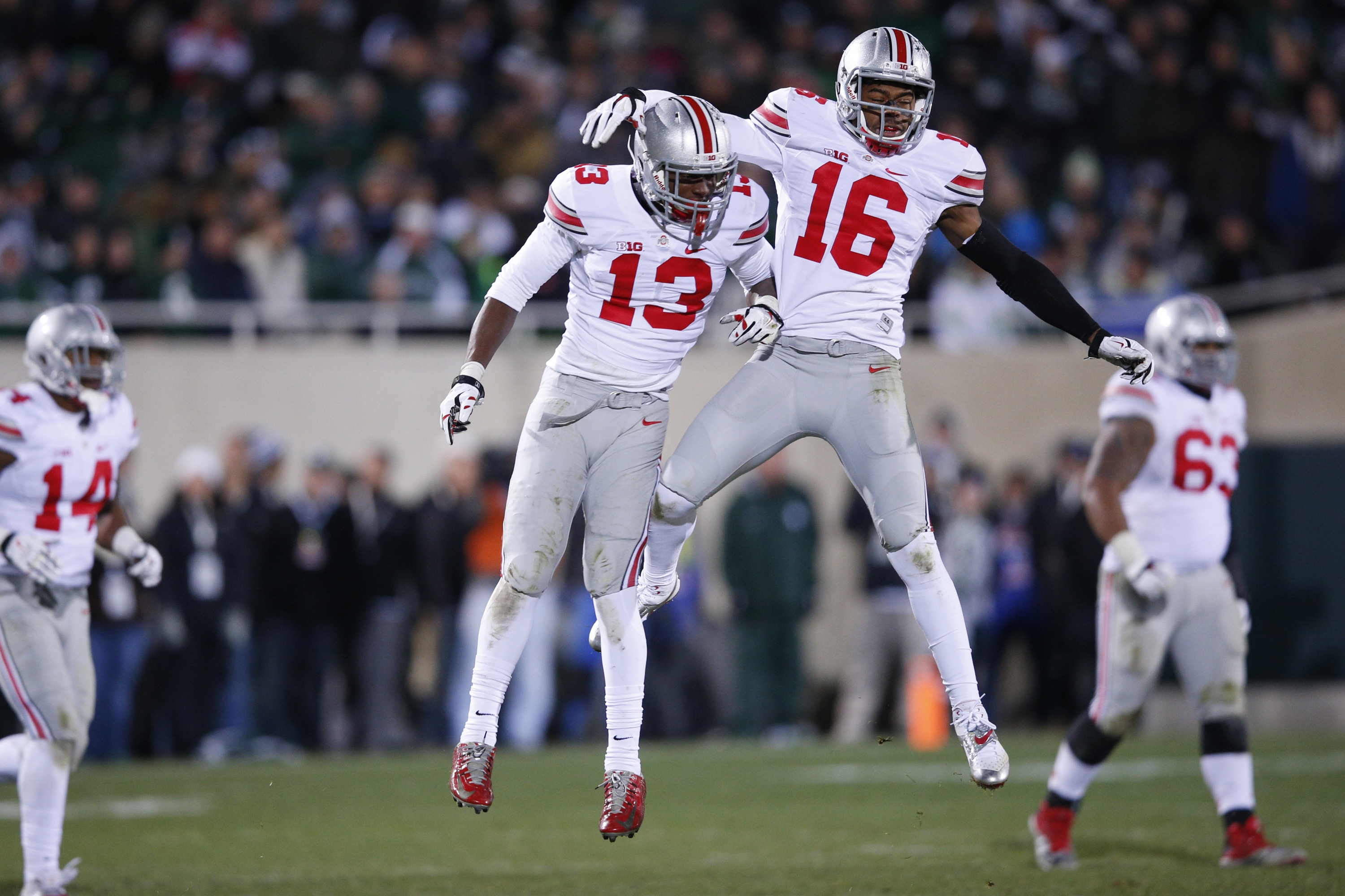 EAST LANSING, MI - NOVEMBER 8: Cam Burrows #16 and Eli Apple #13 of the Ohio State Buckeyes celebrate a defensive stop in the second half of the game against the Michigan State Spartans at Spartan Stadium on November 8, 2014 in East Lansing, Michigan. (Photo by Joe Robbins/Getty Images)