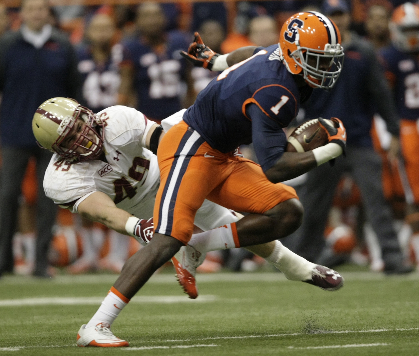 Syracuse's Ashton Broyld, right, runs past Boston College's Steele Divitto, left, in the first quarter of an NCAA college football game in Syracuse, N.Y., Saturday, Nov. 30, 2013. (AP Photo/Nick Lisi)