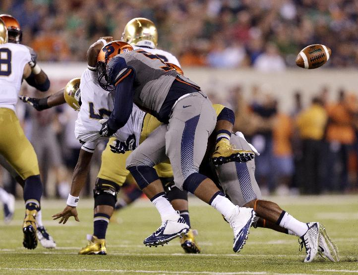 Notre Dame quarterback Everett Golson (5) loses the ball after being hit by Syracuse defensive end Isaiah Johnson, front, and linebacker Cameron Lynch during the first half of an NCAA college football game, Saturday, Sept. 27, 2014, in East Rutherford, N.J. (AP Photo/Julio Cortez)