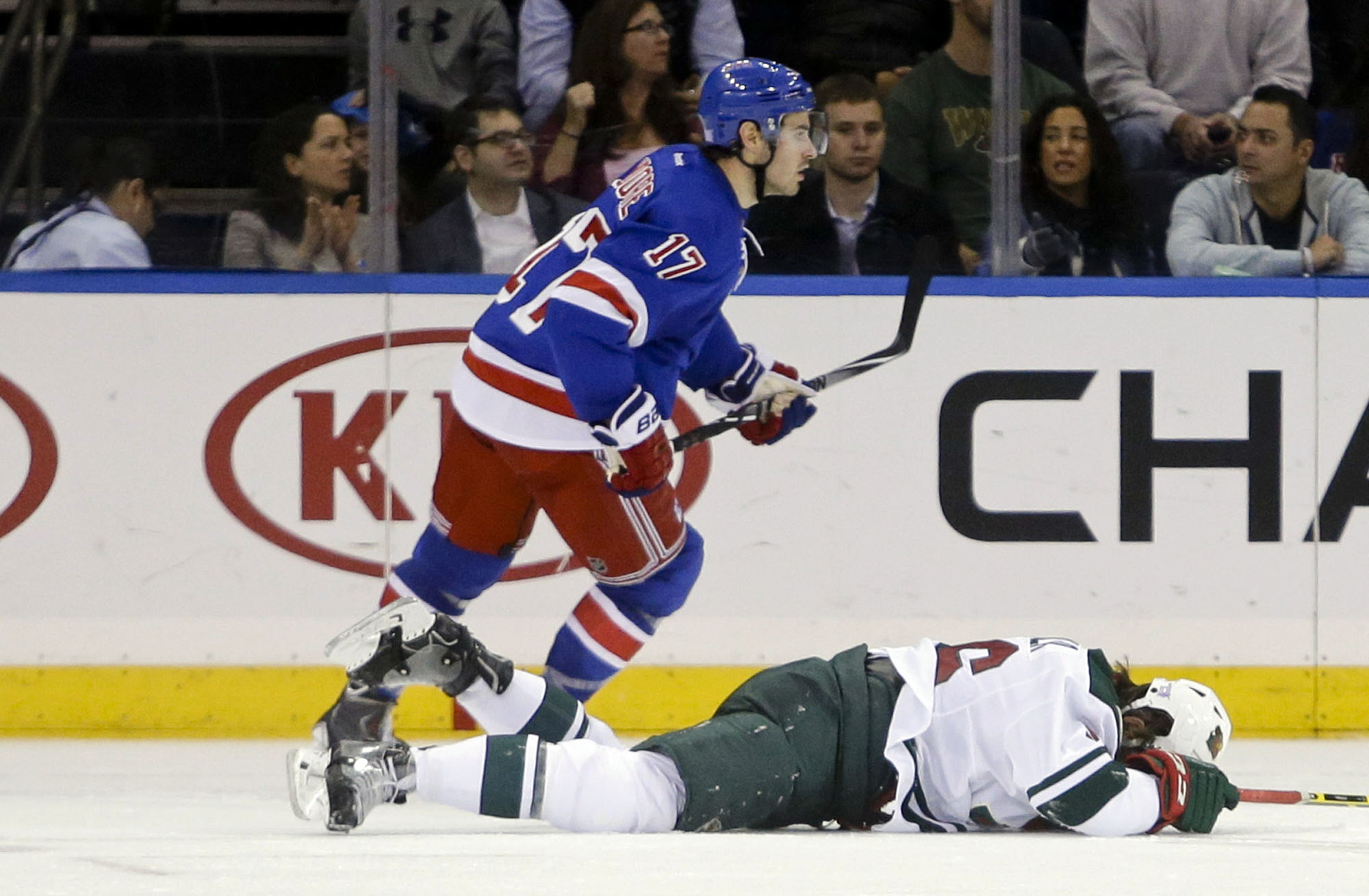 Minnesota Wild's Erik Haula, bottom, holds his head after being hit by New York Rangers' John Moore (17) during the second period of an NHL hockey game Monday, Oct. 27, 2014, in New York. Moore was given a match penalty for the hit. (AP Photo/Frank Franklin II)