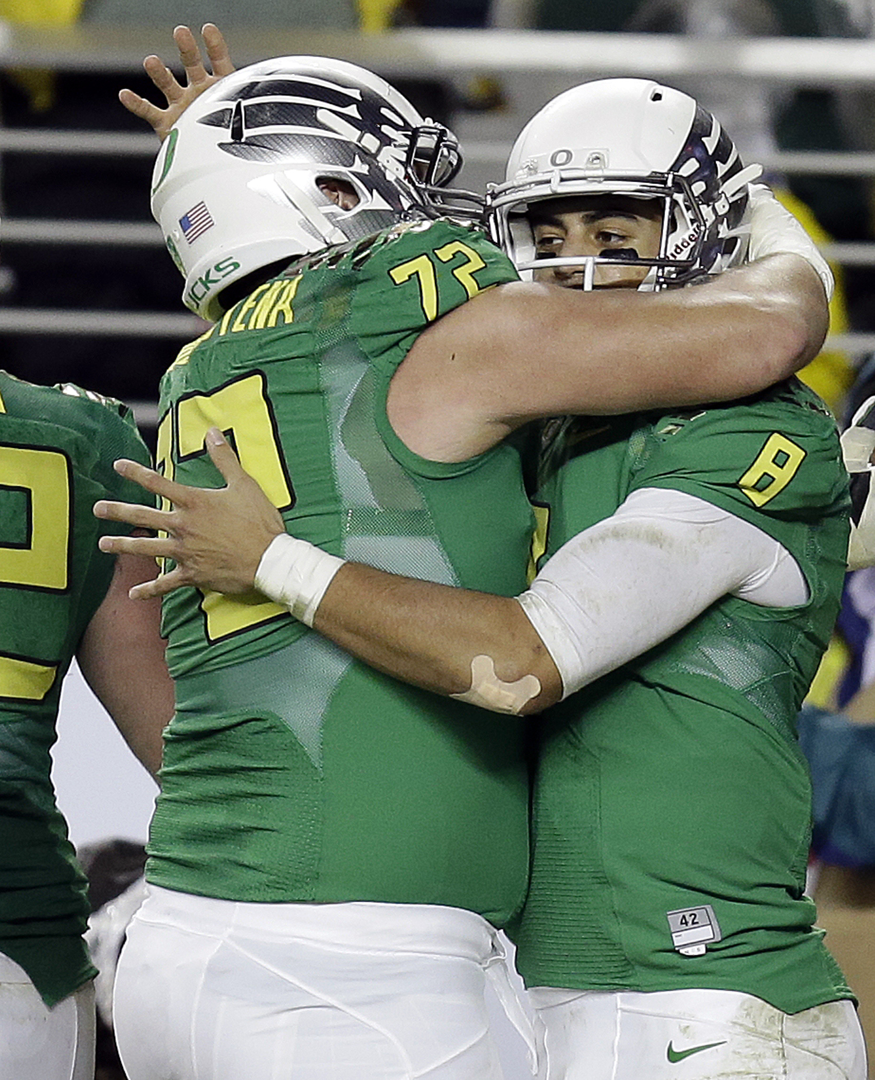 Oregon quarterback Marcus Mariota, right, is congratulated by Andre Yruretagoyena (72) after Mariota scored a touchdown against Arizona during the Pac-12 Conference championship. (AP Photo/Ben Margot)