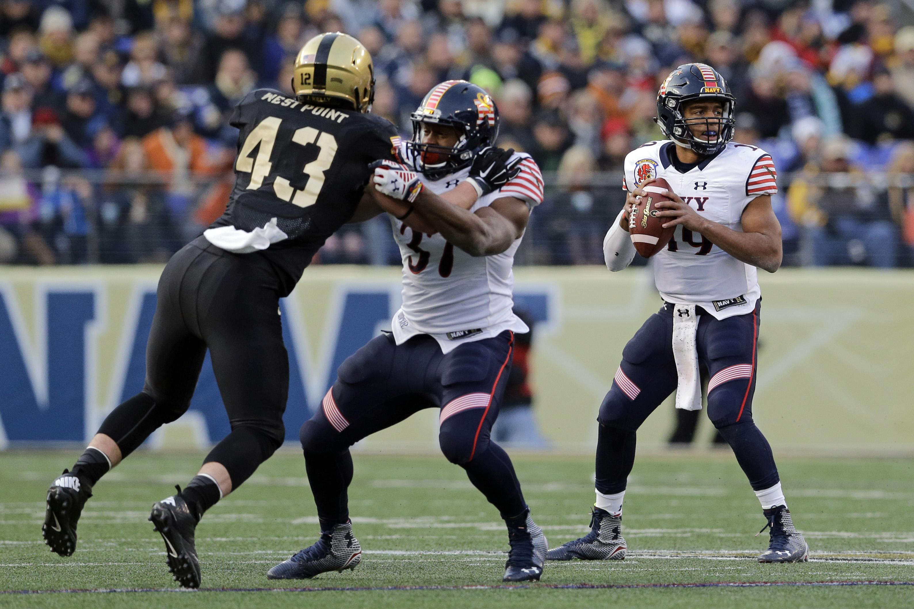 Navy quarterback Keenan Reynolds, right, looks for a receiver as teammate Chris Swain blocks Army linebacker James Kelly. Saturday, Dec. 13, 2014, in Baltimore. (AP Photo/Patrick Semansky)