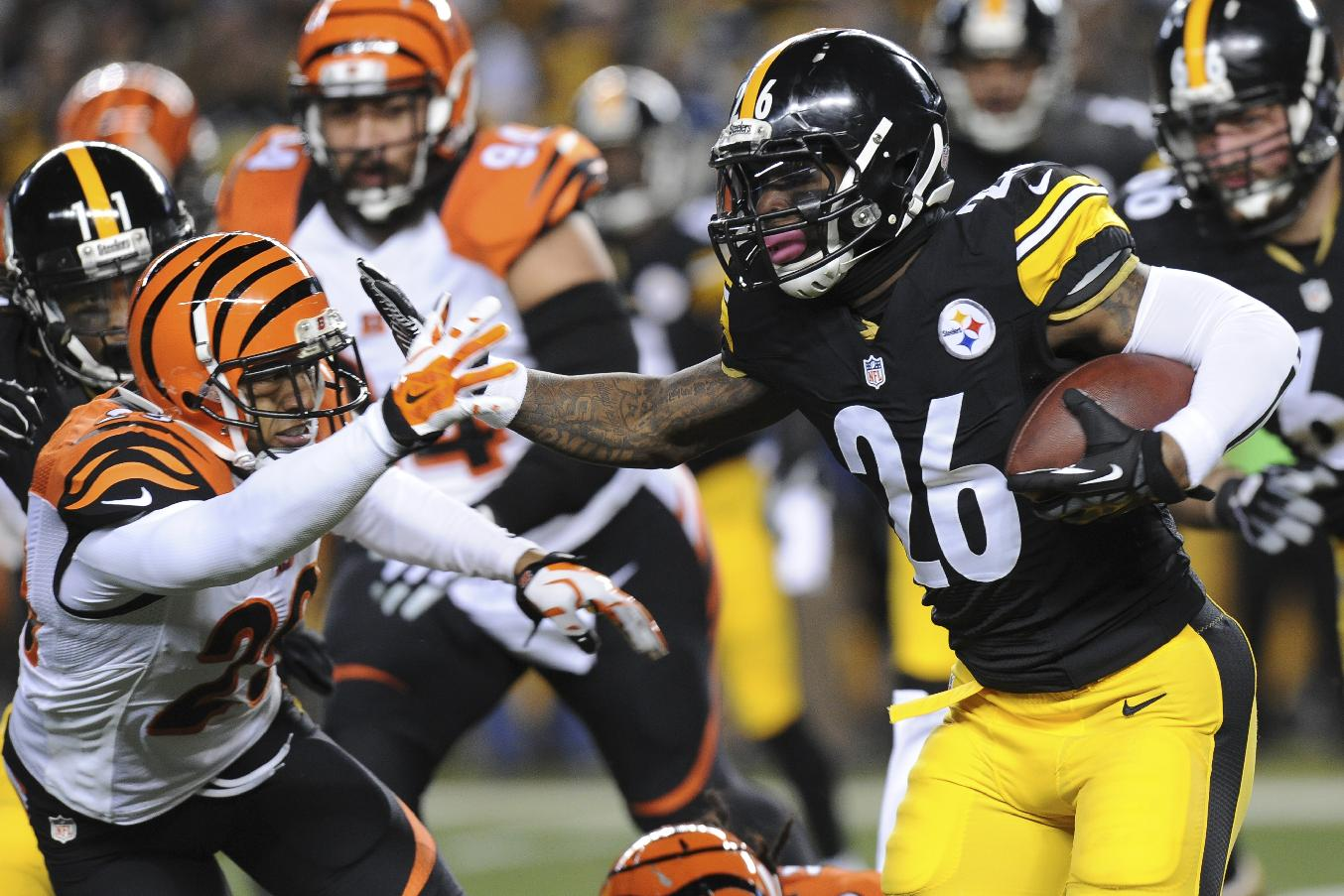 Pittsburgh Steelers running back Le'Veon Bell (26) runs into Cincinnati Bengals cornerback Leon Hall (29) during the first half an NFL football game Sunday, Dec. 28, 2014, in Pittsburgh. (AP Photo/Don Wright)