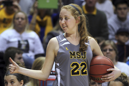 In this Nov. 2, 2014, file photo, Mount St. Joseph's Lauren Hill gives a thumbs-up as she holds the game ball during her first NCAA college basketball game against Hiram University at Xavier University in Cincinnati.(AP Photo/Tom Uhlman, File)