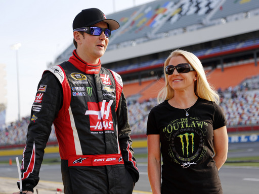 FILE - In this May 22, 2014, file photo, Kurt Busch, left, walks with Patricia Driscoll before qualifying for a NASCAR Sprint Cup series auto race at Charlotte Motor Speedway in Concord, N.C. The police investigation into allegations that NASCAR driver Kurt Busch assaulted his ex-girlfriend has been finished and forwarded to Delaware state prosecutors to decide whether charges will be filed. Cpl. Mark Hoffman with the Dover Police Department said Tuesday, Jan. 6, 2015, that the agency's investigation into the allegations was finished, but he declined to say whether investigators were recommending that Busch be charged. (AP Photo/Terry Renna)