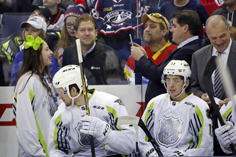 Team Toews head coach Peter Laviolette, second from right rear, takes a picture of his daughter, left, who joined him behind the bench during the first period of the NHL All-Star hockey game in Columbus, Ohio, Sunday, Jan. 25, 2015. Team Toews won 17-12. (AP Photo/Gene J. Puskar)