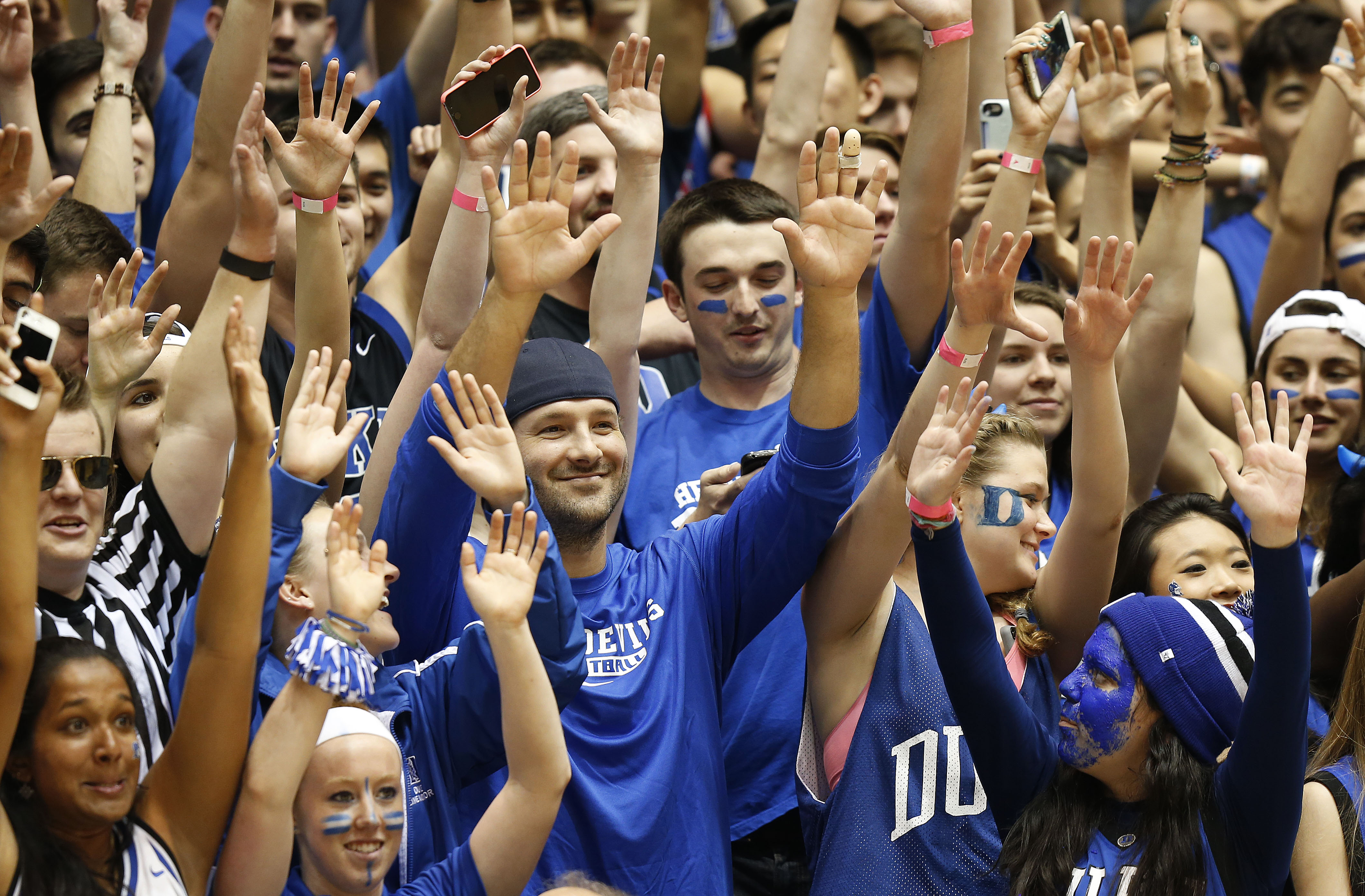 Dallas Cowboys quarterback Tony Romo, center left with baseball cap, cheers with the Cameron Crazies during the second half of Duke's NCAA college basketball game against Wake Forest on Wednesday, March 4, 2015, in Durham, N.C. Duke won 94-51. (AP Photo/Ellen Ozier)