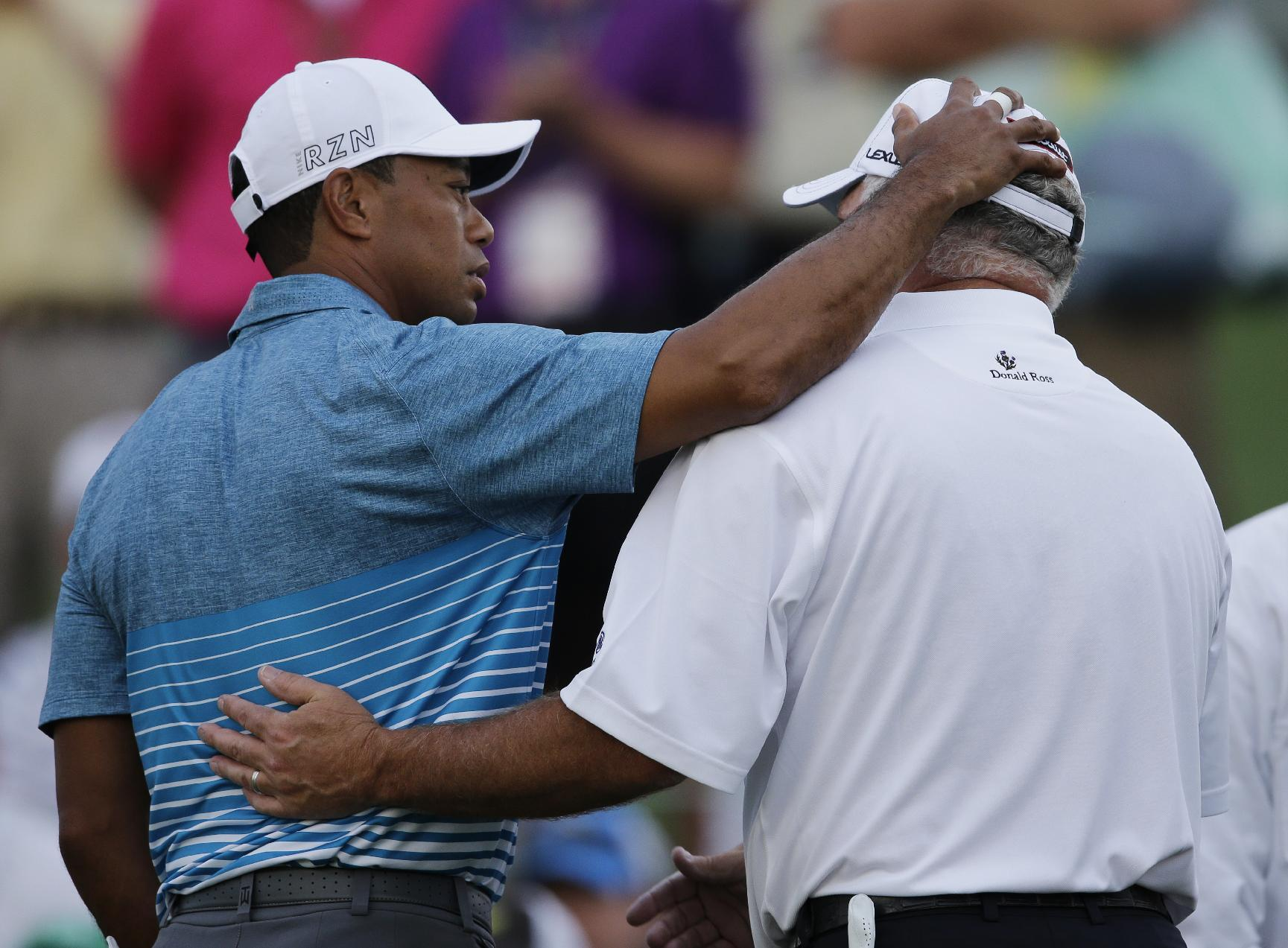 Tiger Woods, left, hugs, Mark O'Meara after their practice round for the Masters golf tournament Monday, April 6, 2015, in Augusta, Ga. (AP Photo/Matt Slocum)