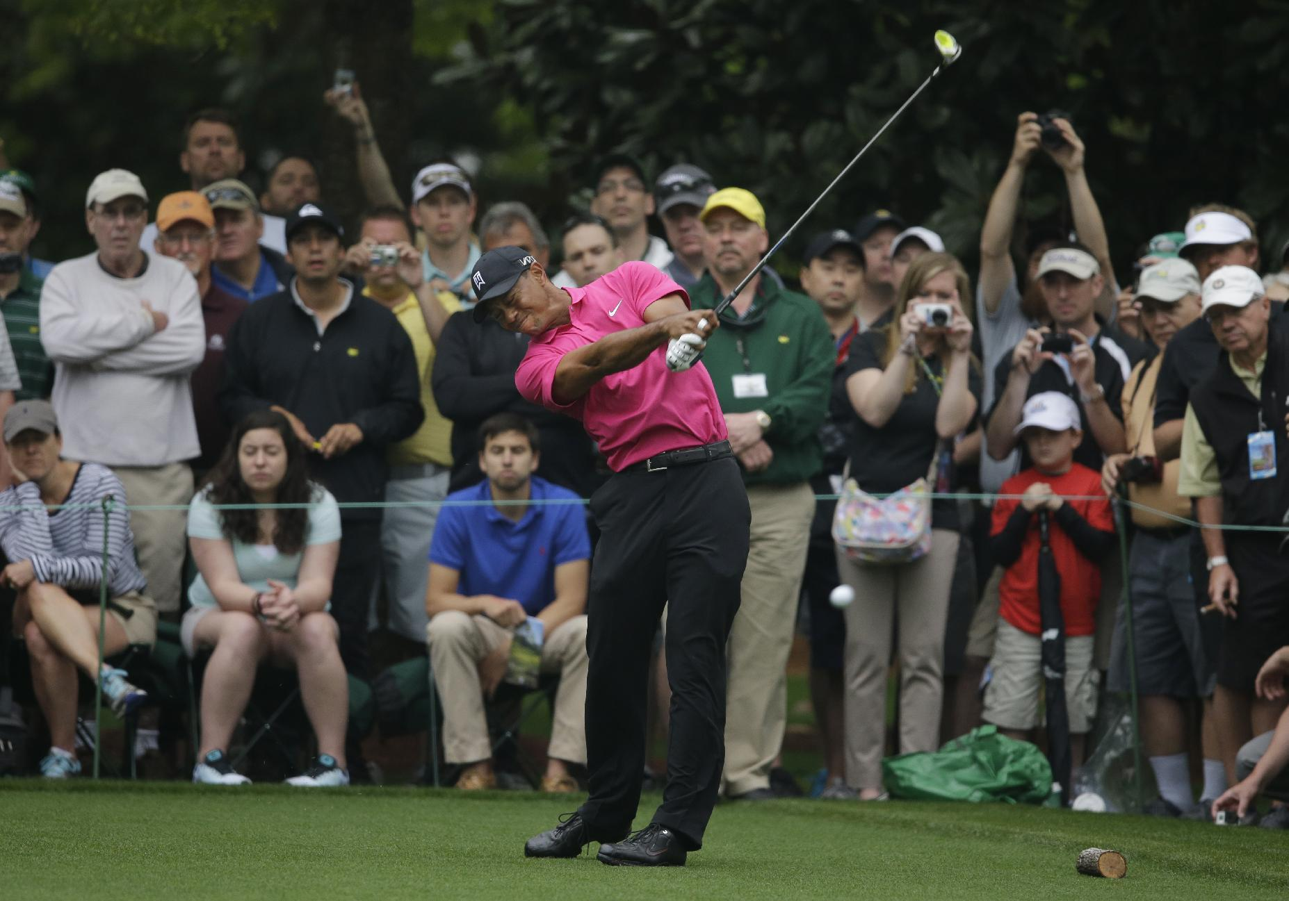 Tiger Woods grimaces as he tees off on the seventh hole during a practice round for the Masters golf tournament Tuesday, April 7, 2015, in Augusta, Ga. (AP Photo/Matt Slocum)