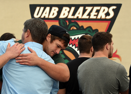 FILE - In this Dec. 2, 2014, file photo, UAB offensive tackle Steve Pickern hugs UAB supporter Justin Craft after UAB President Ray Watts announced the shut down of the UAB football program in Birmingham, Ala. (AP Photo/AL.com, Joe Songer, File)