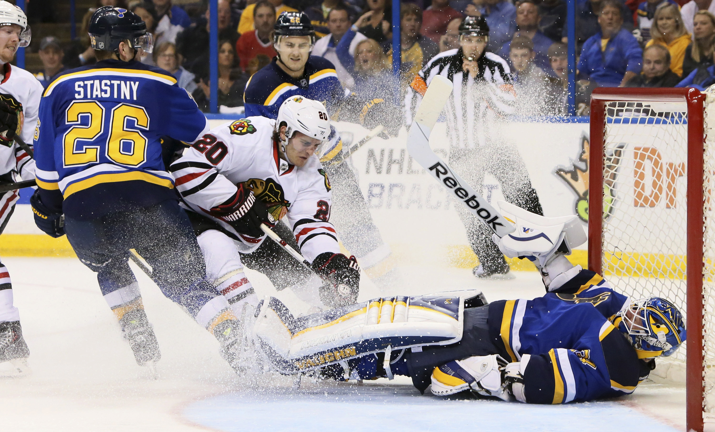 St. Louis Blues goaltender Jake Allen falls back on the puck to cover it up while being pressured by Chicago Blackhawks left wing Brandon Saad (20) during the second period of an NHL hockey game Thursday, April 9, 2015, in St. Louis. (AP Photo/St. Louis Post-Dispatch, Chris Lee)