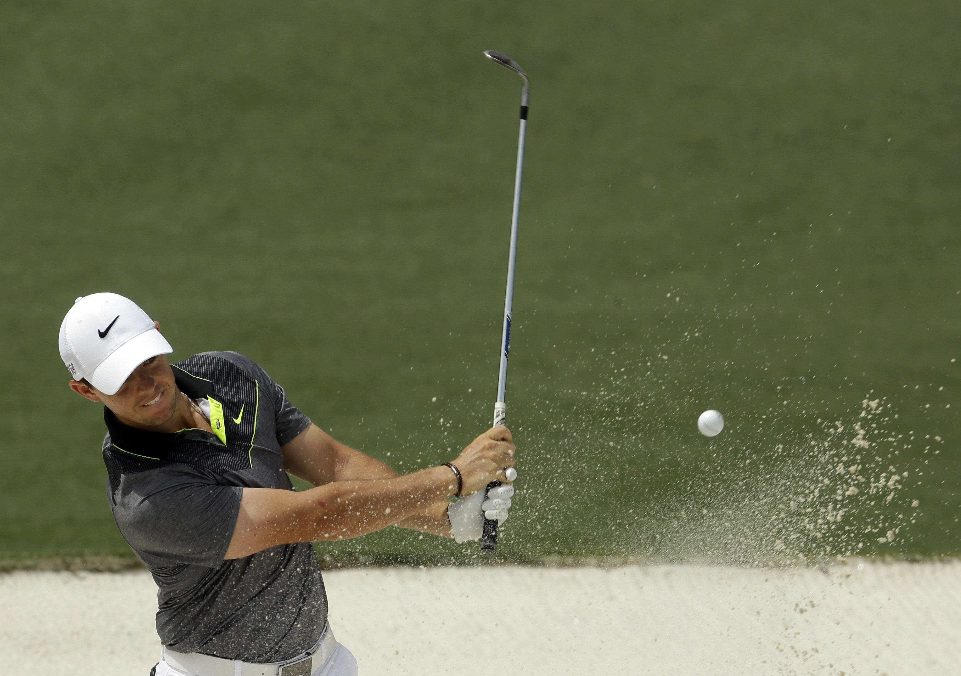 Rory McIlroy, of Northern Ireland, hits out of a bunker on the second hole during the second round of the Masters golf tournament Friday, April 10, 2015, in Augusta, Ga. (AP Photo/Darron Cummings)