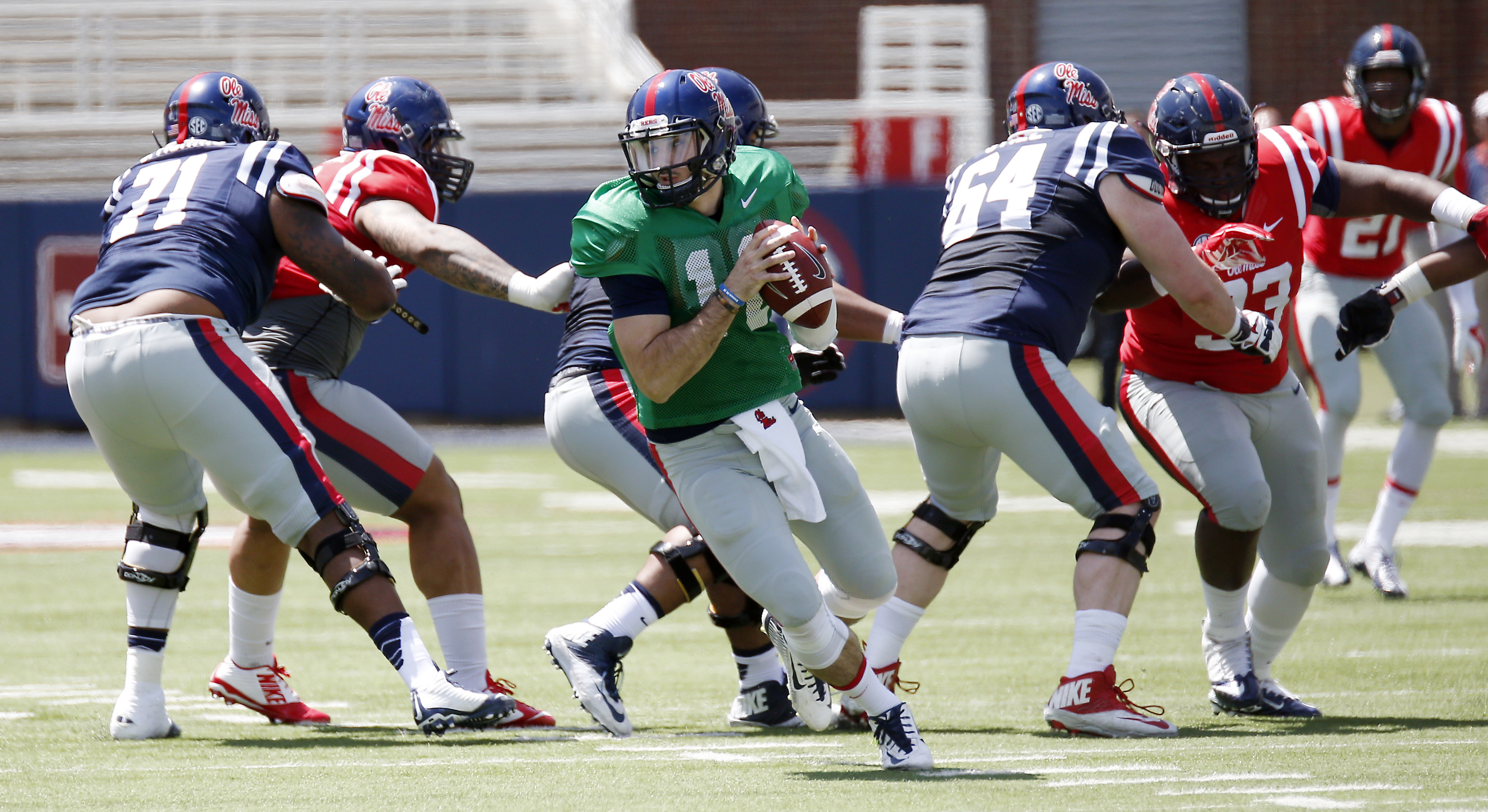 Mississippi Blue quarterback Chad Kelly (10) rolls out of the pocket as he tries to find an open receiver while Red defenders pursue during their spring college football game, Saturday, April 11, 2015, in Oxford, Miss. (AP Photo/Rogelio V. Solis)