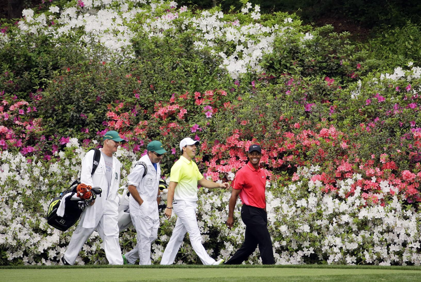 Tiger Woods, right, walks with Rory McIlroy, of Northern Ireland, and their caddies. (AP)