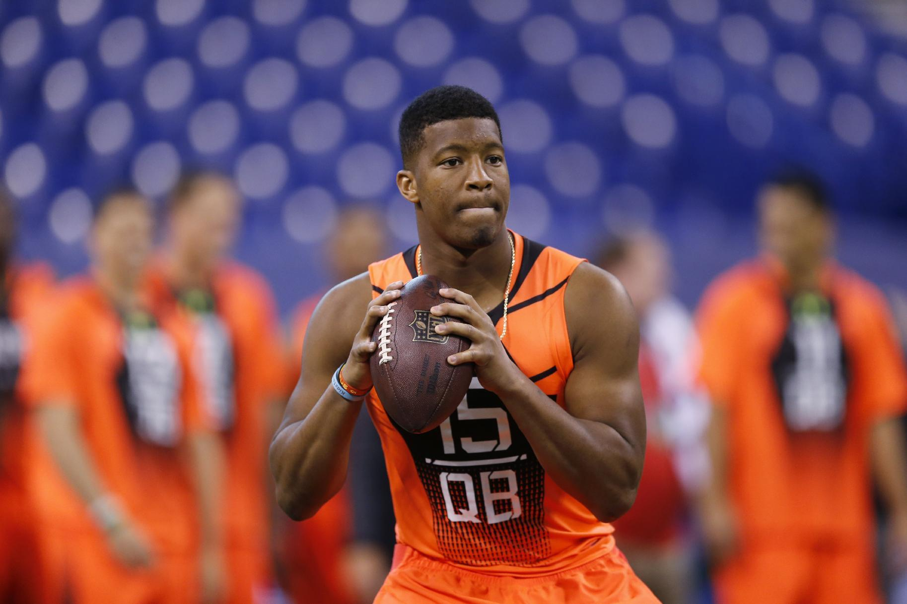 FILE - In this Feb. 21, 2015, file photo, Florida State quarterback Jameis Winston runs a drill at the NFL football scouting combine in Indianapolis. While 26 draft-eligible players have accepted invitations from the NFL to attend the proceedings later this month, Winston and Marcus Mariota are not among them. The two most recent Heisman Trophy winners and highest-profile players in this year's crop have opted to stay home with their families for the April 30-May 2 draft. (AP Photo/Julio Cortez, File)