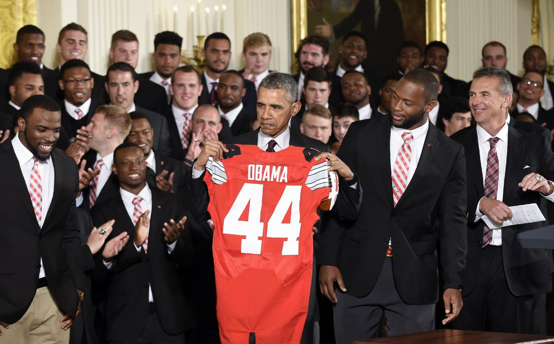President Barack Obama holds up a Ohio State football jersey that he was presented with from Ohio State football players Curtis Grant and Doran Grant, as head coach Urban Meyer watches at right. (AP Photo/Susan Walsh)