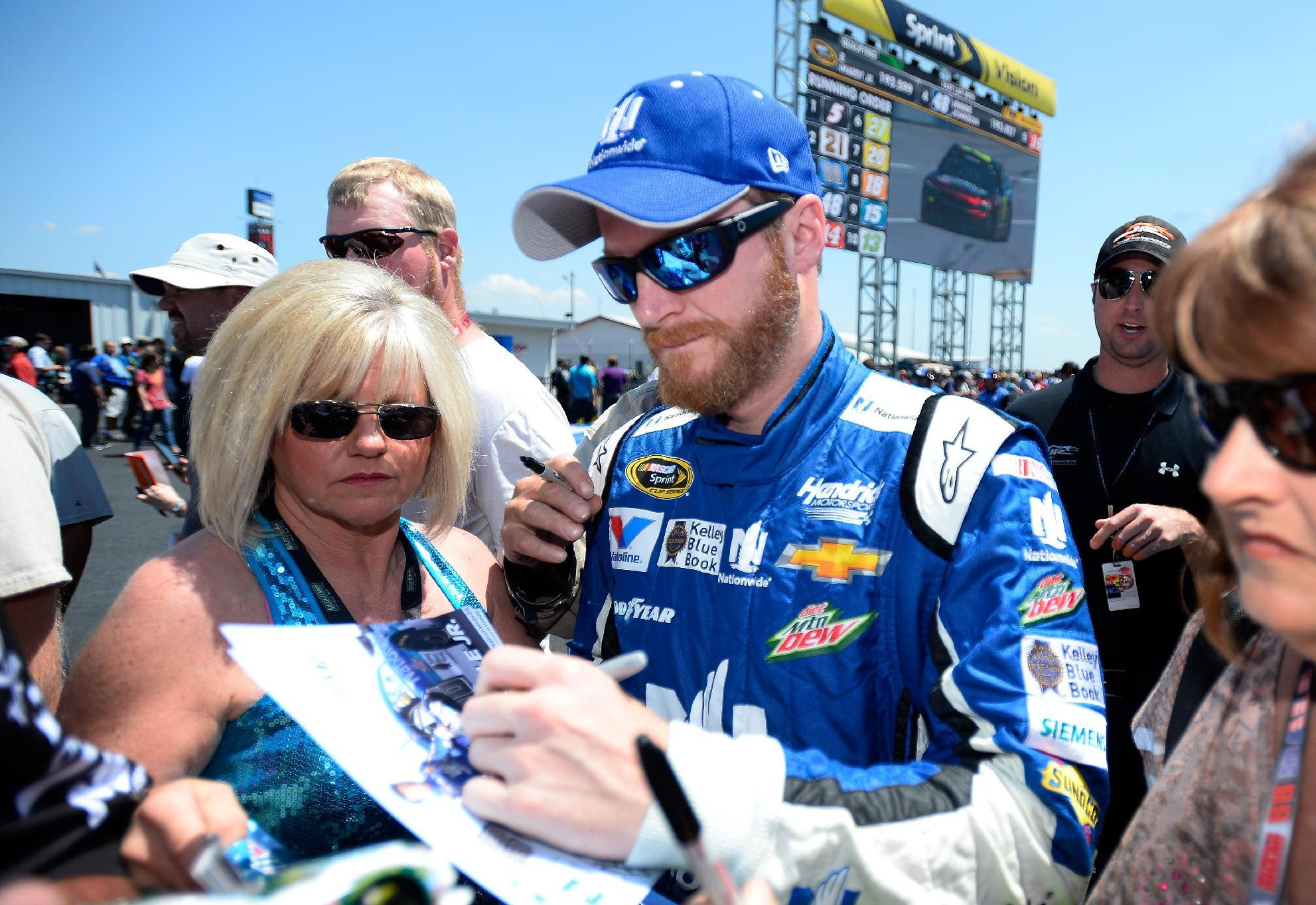Dale Earnhardt Jr. signs autographs during qualifying for Sunday's NASCAR Sprint Cup Series auto race at Talladega Superspeedway, Saturday, May 2, 2015, in Talladega, Ala. (AP Photo/David Tulis)