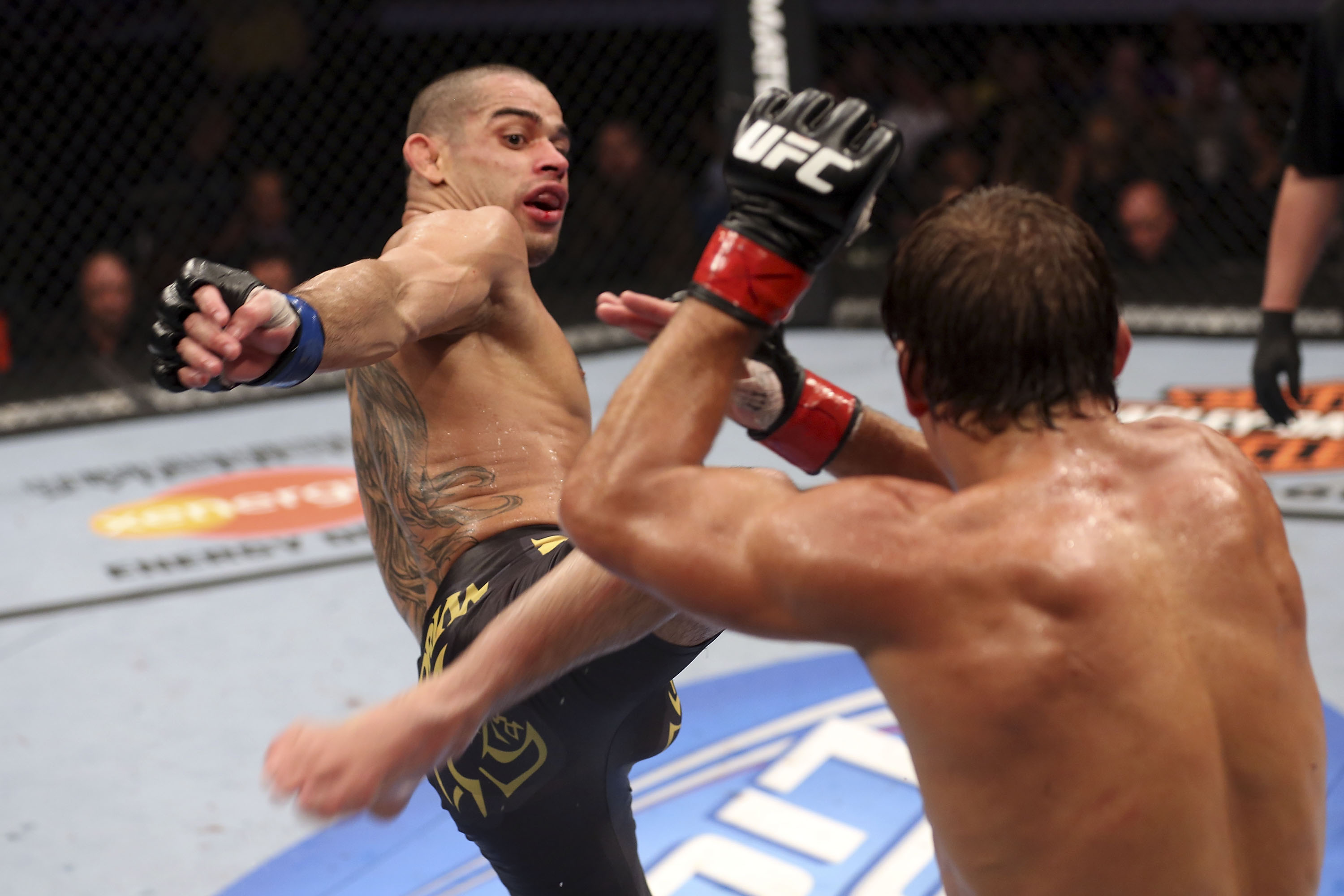 Renan Barao, left, goes on the offensive against Urijah Faber. (Getty Images)