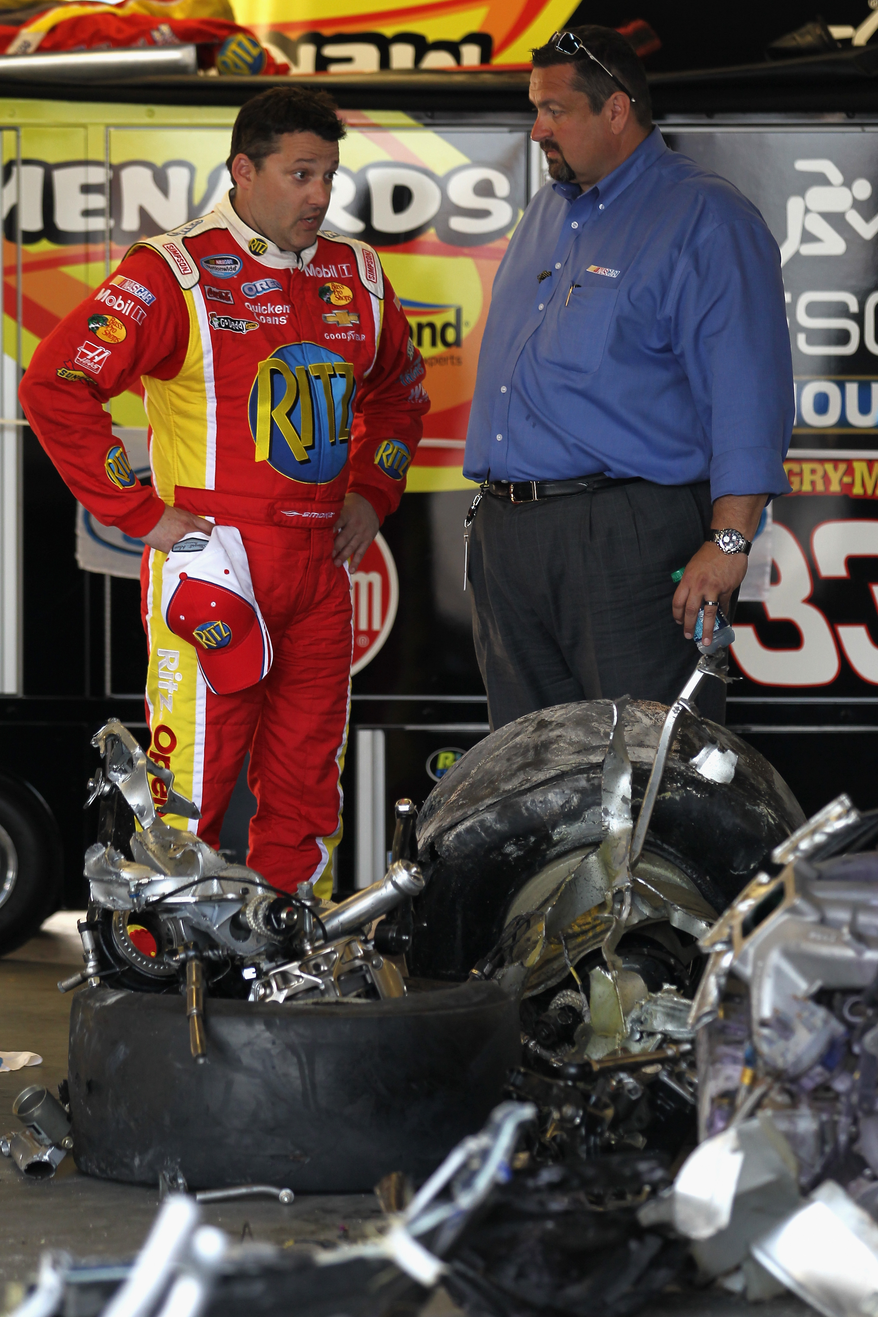 Tony Stewart, left, looks at the debris of the car driven by Kyle Larson. (Getty Images)