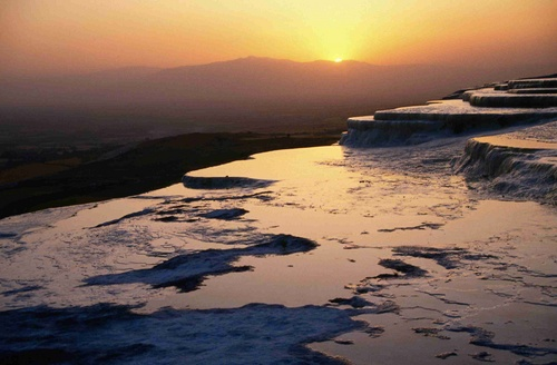 Calcium laden mineral waters cascade over the cliffs of Pamukkale, and as it cools the calcium, it precipitates and clings to the cliffs forming the snow like waterfalls of white stone, however, due to circumstances the site has deteriorated substantially