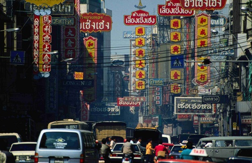 Traffic on the streets of Chinatown, surrounded by buildings bearing signs - Bangkok