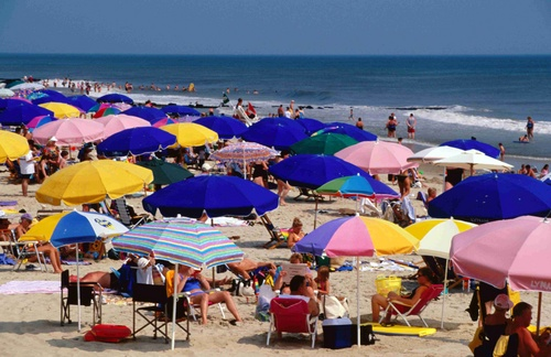 Colourful beach umbrellas and crowd on Rehoboth Beach.