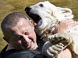 Polar bear Knut and his keeper Ronny Henkel play in the water at the Zoo in Berlin on Monday, June 11, 2007. (AP Photo/ Michael Sohn)