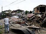 A man walks past a collapsed house in Kashiwazaki, northern Japan. (REUTERS/Kiyoshi Ota)