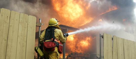 Firefighters from the Orange County A firefighter tries to knock down flames on a home completely engulfed in hopes of saving neighboring homes in the community of Rancho Bernardo, San Diego, Calif., Monday, Oct 22. 2007.