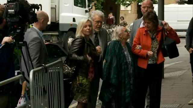 Rolf Harris walks into court with family